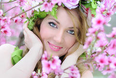 Beautiful girl in a flowered garden peach Royalty Free Stock Photos