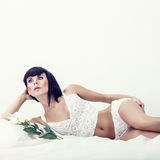 Beautiful girl with flowers on the bed Stock Photos