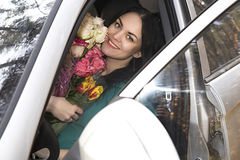 Beautiful girl with flowers in the car stock photos
