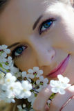 The beautiful girl among flowers in garden Royalty Free Stock Image