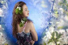 Beautiful girl with flowers in hair on flower background Stock Images