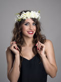 Beautiful girl with flowers in hair posing in black shirt looking at camera Royalty Free Stock Image