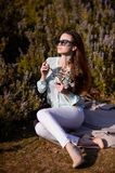 Beautiful girl with flowers in hands outdoors. Spring sunny day royalty free stock images