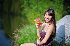 Beautiful girl with flowers in hands sitting on green grass Stock Image