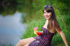 Beautiful girl with flowers in hands sitting on green grass Royalty Free Stock Images