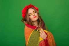 Beautiful girl with flowers in her hair hiding a blanket Stock Photo