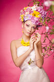 Beautiful girl with flowers in her hair. Spring. Young lady on a pink background with flower crown Royalty Free Stock Photos