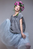 Beautiful girl with flowers on her head in fashion clothes posing against the background in the studio. Stock Images
