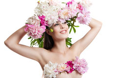Beautiful girl with flowers peonies. Portrait of a young woman with flowers in her hair and a dress of flowers. Stock Photo