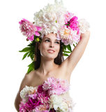 Beautiful girl with flowers peonies. Portrait of a young woman with flowers in her hair and a dress of flowers. Royalty Free Stock Images
