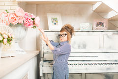 Beautiful girl with flowers at the piano Royalty Free Stock Images