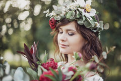 Beautiful girl with flowers. Portrait of young beautiful girl with flowers in circlet of flowers Royalty Free Stock Image