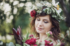 Beautiful girl with flowers. Portrait of young beautiful girl with flowers in circlet of flowers Stock Photo