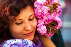Beautiful Girl with flowers, Spring Magic. Sakura pink flowers Royalty Free Stock Photography
