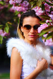 Beautiful Girl with flowers, Spring Magic. Sakura pink flowers. With glamour white fur, and sunglasses. Royalty Free Stock Photography