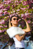 Beautiful Girl with flowers, Spring Magic. Sakura pink flowers. With glamour white fur, and sunglasses. Stock Images