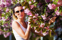 Beautiful Girl with flowers, Spring Magic. Sakura pink flowers. With glamour white fur, and sunglasses. Royalty Free Stock Photo