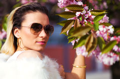 Beautiful Girl with flowers, Spring Magic. Sakura pink flowers. With glamour white fur, and sunglasses Royalty Free Stock Photos