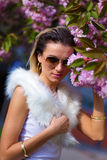 Beautiful Girl with flowers, Spring Magic. Sakura pink flowers. With glamour white fur, and sunglasses Stock Photos