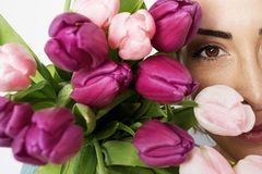 Beautiful girl with flowers tulips in hands on a light background. Closeup portrait.  stock photos