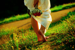 Beautiful girl with flowers walking at sunset Royalty Free Stock Photography