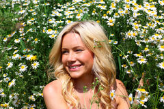 Beautiful girl in the flowers. Beautiful young blond woman smiling on a field in bloom stock photography