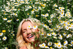 Beautiful girl in the flowers. Beautiful young blond woman smiling on a field in bloom Stock Photo