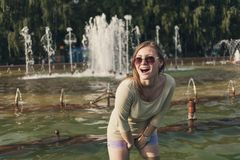Girl with flowing hair in short shorts and sunglasses is standing in the fountain royalty free stock photos