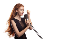Beautiful girl with flowing hair singing into retro microphone Royalty Free Stock Image