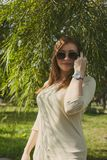 Girl with flowing hair in sunglasses looks into the frame, raising a hand to her face royalty free stock photos