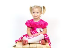 Little girl 3 years old in a red dress with bows in her hair. Beautiful girl in a beautiful fluffy dress posing against a white wall stock photography