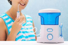 Beautiful girl flushes her teeth with an oral irrigator. the woman smiles and holds the irrigator handle. cleaning of teeth at hom. E with a compact device stock photos