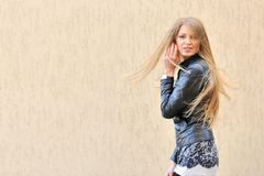 Beautiful girl with fluttering hair. Young beautiful girl with fluttering hair on wall stock photo