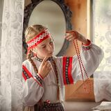 A beautiful girl in a folk costume looks at the Rowan berry beads