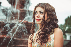 Beautiful girl at the fountain. Girl with long hair near the fountain.Beautiful woman standing near the fountain Stock Images