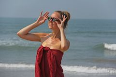 Beautiful girl freak in a red dress and blond hair, on the backg royalty free stock image