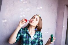 Beautiful girl with freckles blowing bubbles near pink wall royalty free stock photography
