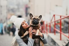 Beautiful girl with French bulldog. Beautiful brunette woman holding her adorable French bulldog stock photo