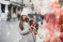 Beautiful girl with French bulldog. Beautiful brunette woman standing with her adorable French bulldog next to candies selling on street royalty free stock photo