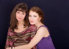 Beautiful girl-friends. Portrait of two beautiful girl-friends on black background Stock Photo