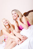 2 beautiful girl friends or sisters pretty cute blond young women in pajamas sitting on white bed having fun happy smiling. Two pretty cute young blond women in Stock Image
