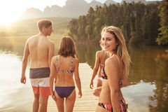 Beautiful girl with friends and walking on the jetty. Portrait of beautiful young girl in bikini looking over her shoulder with her friends on pier. Group of Stock Image