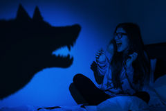 Beautiful girl frightened from wolf shadow Stock Photo