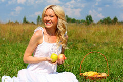 Beautiful girl with fruit smiling. Beautiful fruit basket on the grass stock photo