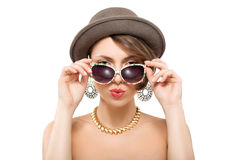 Beautiful girl with funny face. Funny summer portrait of girl in hat with funny face, holding sunglasses with hands Stock Photography