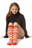 Beautiful girl in funny socks. Beautiful girl with long hair in sweater and long red-orange socks sits on the floor, isolated on white Stock Images