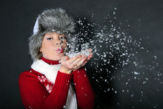The beautiful girl in a fur cap has control over snow Stock Photo