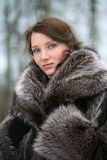 Beautiful girl in a fur coat. Portrait of a smiling beautiful girl in a fur coat from a raccoon on the nature stock photo