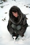 Beautiful girl in a fur coat. Portrait of a smiling beautiful girl in a fur coat from a raccoon on the nature Royalty Free Stock Photography