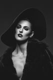 Beautiful girl in fur coat and hat. Beautiful young woman with glamorous make-up in luxurious fur coat on naked body and fashion hat on black background. Copy Stock Photo